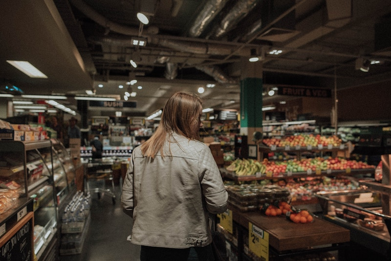 woman walking through produce section