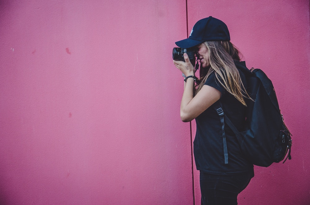 female photographer in front of pink wall