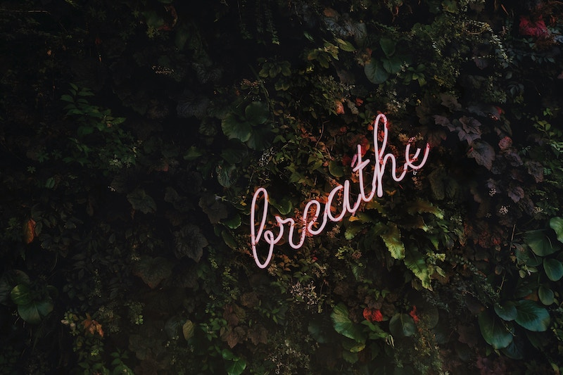 neon sign that says 'breathe'