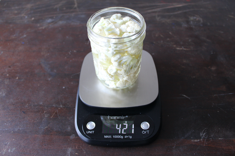 glass jar full of cauliflower and water on digital scale