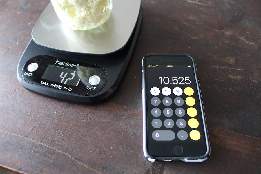 phone calculator next to scale and jar